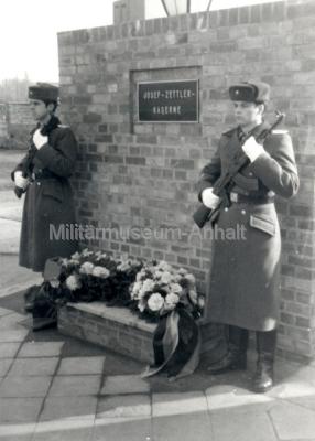 """<p>In Würdigung der gezeigten Leistungen der Angehörigen des Truppenteils bei der Erfüllung der militärischen Hauptaufgabe verlieh Armeegeneral Hoffmann am 01.03.1976 der Kaserne den Ehrennamen """"Josef Zettler"""".<br /><br /></p>"""